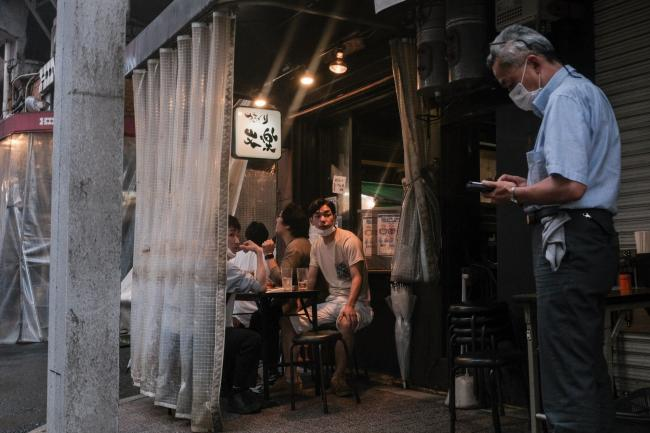 © Bloomberg. Customers dine at an Izakaya bar at the Ameya Yokocho market in the Ueno District of Tokyo, Japan, on Friday, July 2, 2021. Confidence among Japan's large manufacturers rebounded to the highest since 2018 and big businesses of all stripes ramped up investment plans in a sign that companies see an end to the pandemic even as virus restrictions grind on at home.