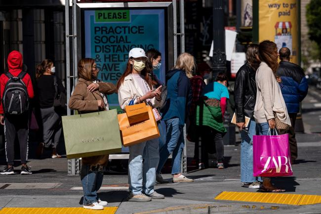 © Bloomberg. Pedestrians carry shopping bags while waiting to cross Geary Street in San Francisco. Photographer: David Paul Morris/Bloomberg