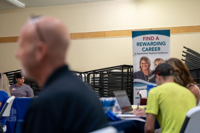© Bloomberg. Appalachian Regional Healthcare signage seeking job applications during a job fair at a community center in Beattyville, Kentucky, U.S., on Wednesday, July 28, 2021. Applications for U.S. state unemployment insurance rose unexpectedly by the most since late March, underscoring week-to-week volatility in an otherwise improving labor market.