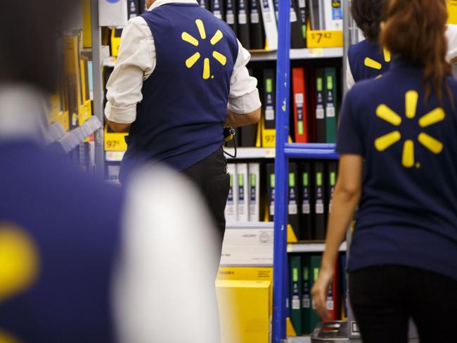 © Bloomberg. Employees restock shelves at Wal-Mart