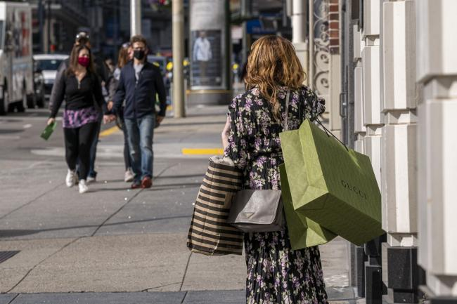 © Bloomberg. A pedestrian carries shopping bags in San Francisco.