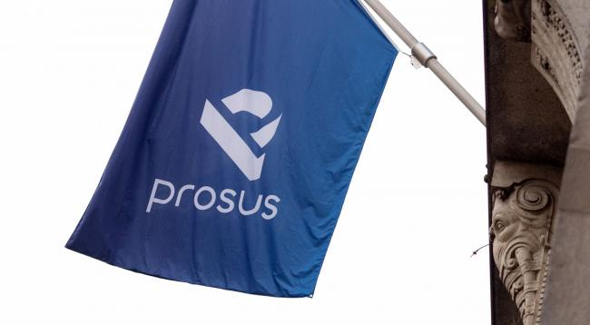 © Bloomberg. A Prosus flag is displayed ahead of the trading debut of the new Prosus NV unit of Naspers Ltd., outside the Amsterdam Stock Exchange, operated by Euronext NV, in Amsterdam, Netherlands, on Wednesday, Sept. 11, 2019. Naspers will retain 73% of the new company, which will house everything from a 31% stake in Chinese online giant Tencent to food delivery and advertising firms from the U.S. to India and Brazil. Photographer: Bloomberg/Bloomberg